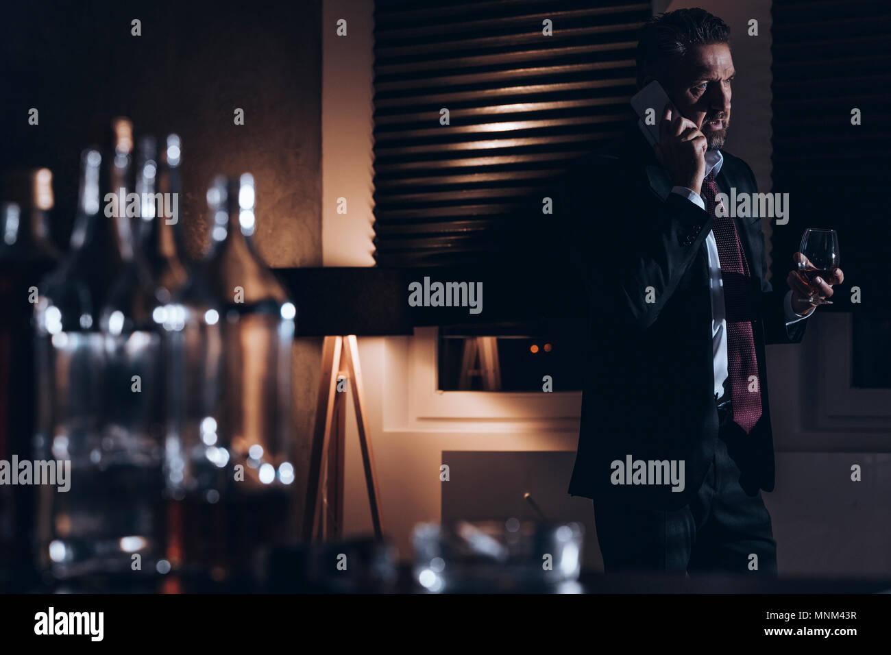 Destacado hombre de mediana edad en traje de hablar por teléfono y sosteniendo un vaso de alcohol mientras está de pie en una habitación oscura con botellas de bebida vacía en un blu Imagen De Stock