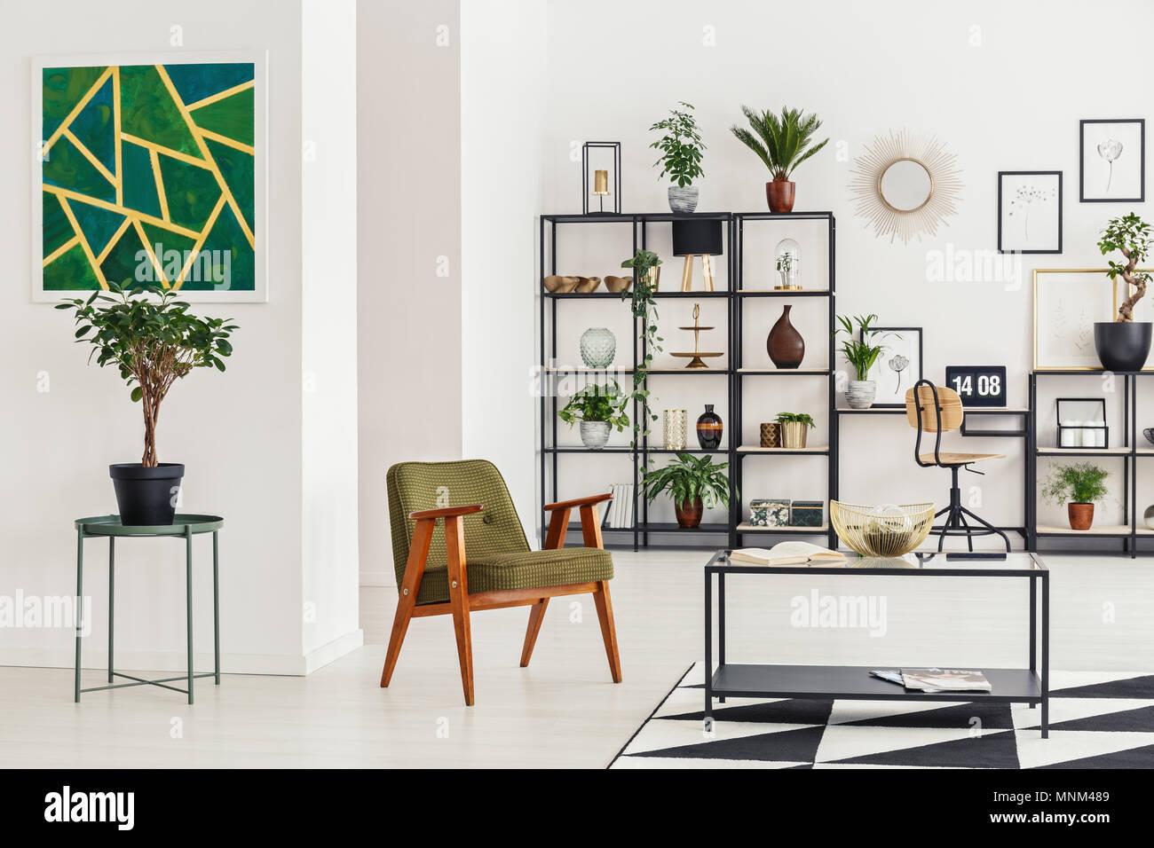 Planta en una mesa contra la pared blanca con pintura verde en el salón interior con sillón de madera Imagen De Stock