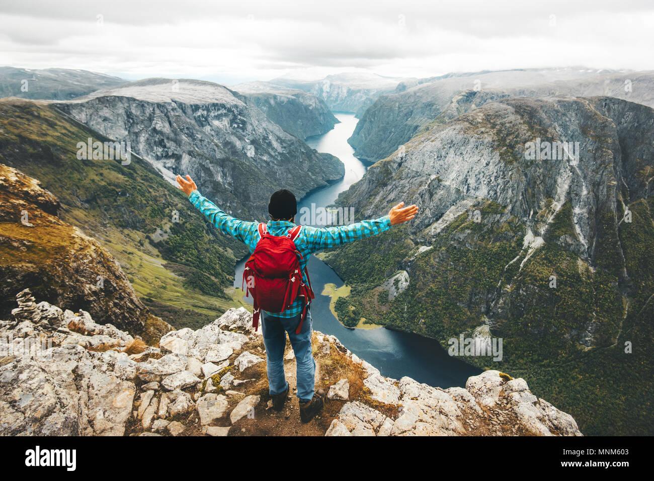Hombre feliz en la montaña cumbre mochilero viajando en Noruega viaje de aventura en el estilo de vida de vacaciones activas por encima Naeroyfjord éxito wellness lif saludable Imagen De Stock