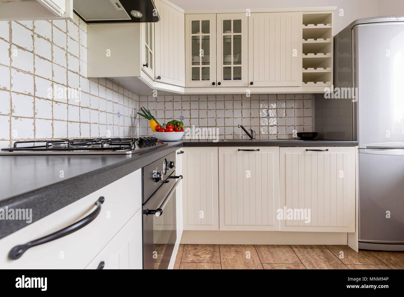 Luz blanca cocina con muebles de madera maciza y encimera. Foto de stock