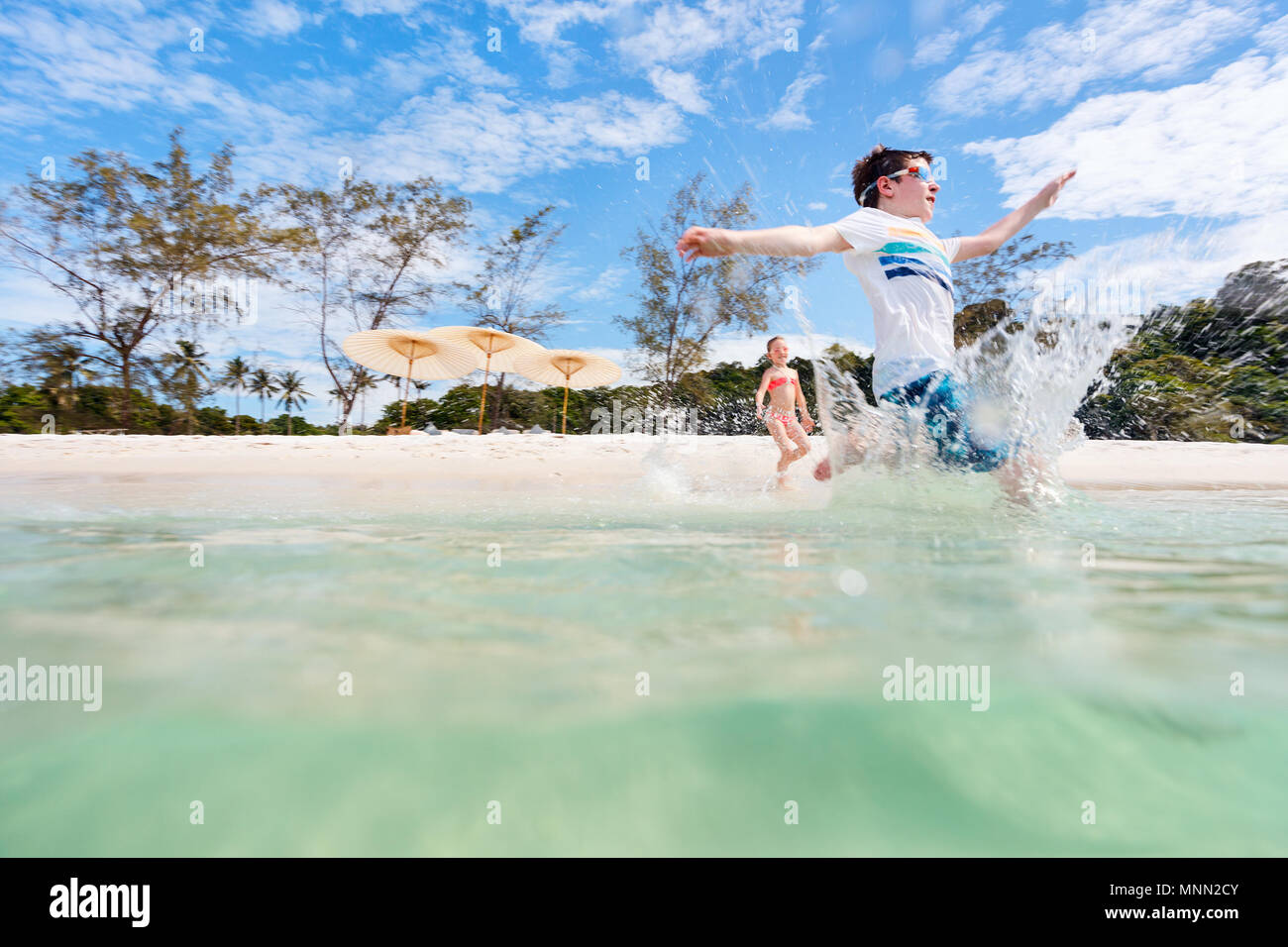 Los niños se diviertan en tropical beach durante las vacaciones de verano jugando juntos en aguas someras Foto de stock