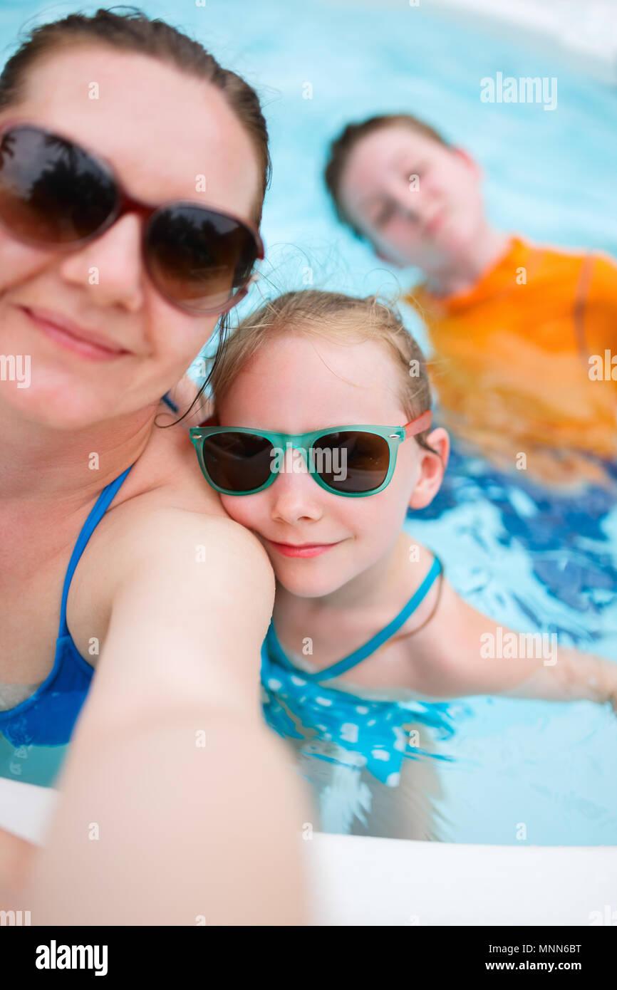 Feliz madre y sus hijos en una piscina al aire libre teniendo selfie en vacaciones tropicales Imagen De Stock