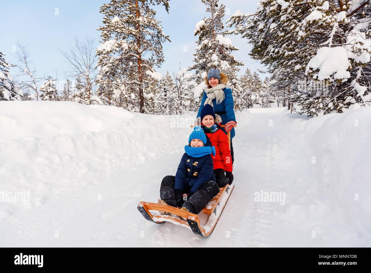 Hermosa familia de la madre y los niños disfrutan día nevado de invierno al aire libre diversión trineo Imagen De Stock