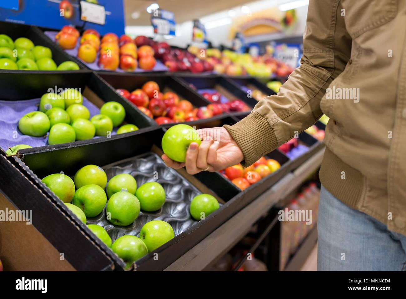 Muchas variedades de manzanas surtidas en escaparate de tienda de ultramarinos casillas en pasillo, supermercado, el hombre persona cliente holding verde granny smith fr Imagen De Stock