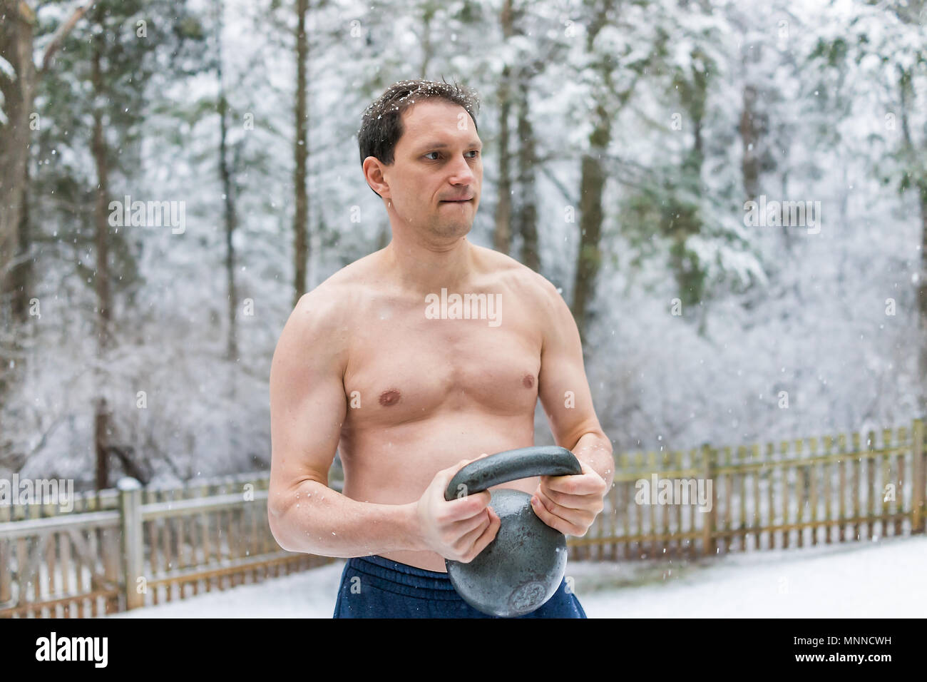 Colocar jóvenes descamisados hombre ejercer con kettlebell pesadas y los músculos en el parque al aire libre fuera de la celebración de levantamiento de peso durante el invierno, la nieve Imagen De Stock