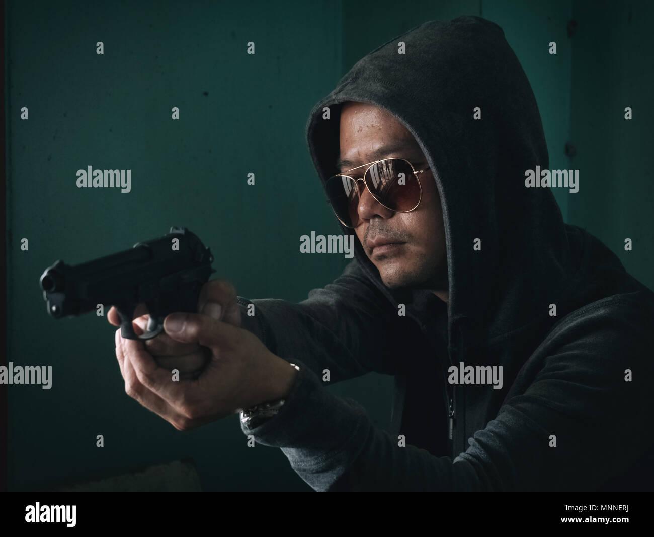 Hombre encapuchado con una pistola en el cuarto oscuro Foto & Imagen ...