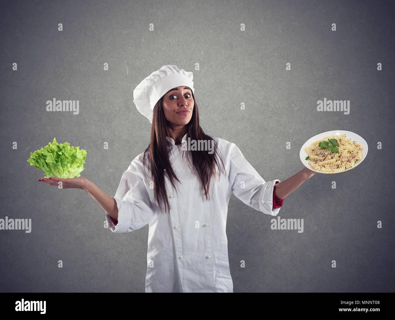 Chef indeciso entre ensalada fresca o plato de pasta Imagen De Stock