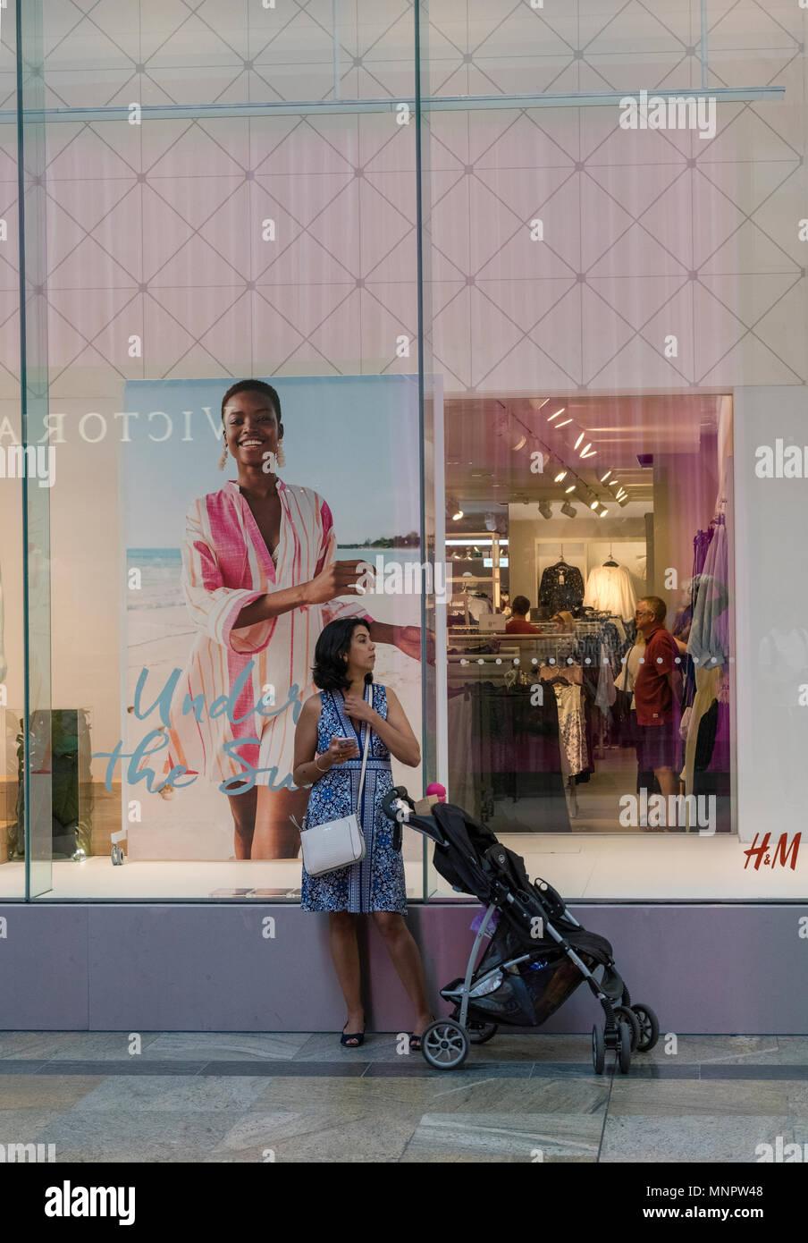 Una mujer joven con un bebé en un cochecito de pie fuera de una tienda de ropa de mujeres en un centro comercial mirando un teléfono móvil o dispositivo portátil. Imagen De Stock