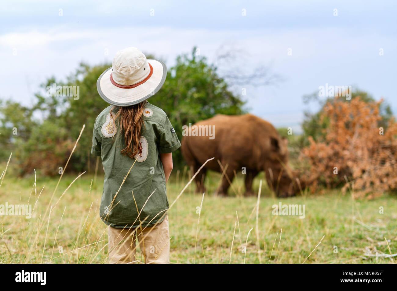 Vista posterior de una niña en safari caminando cerca de White Rhino Imagen De Stock