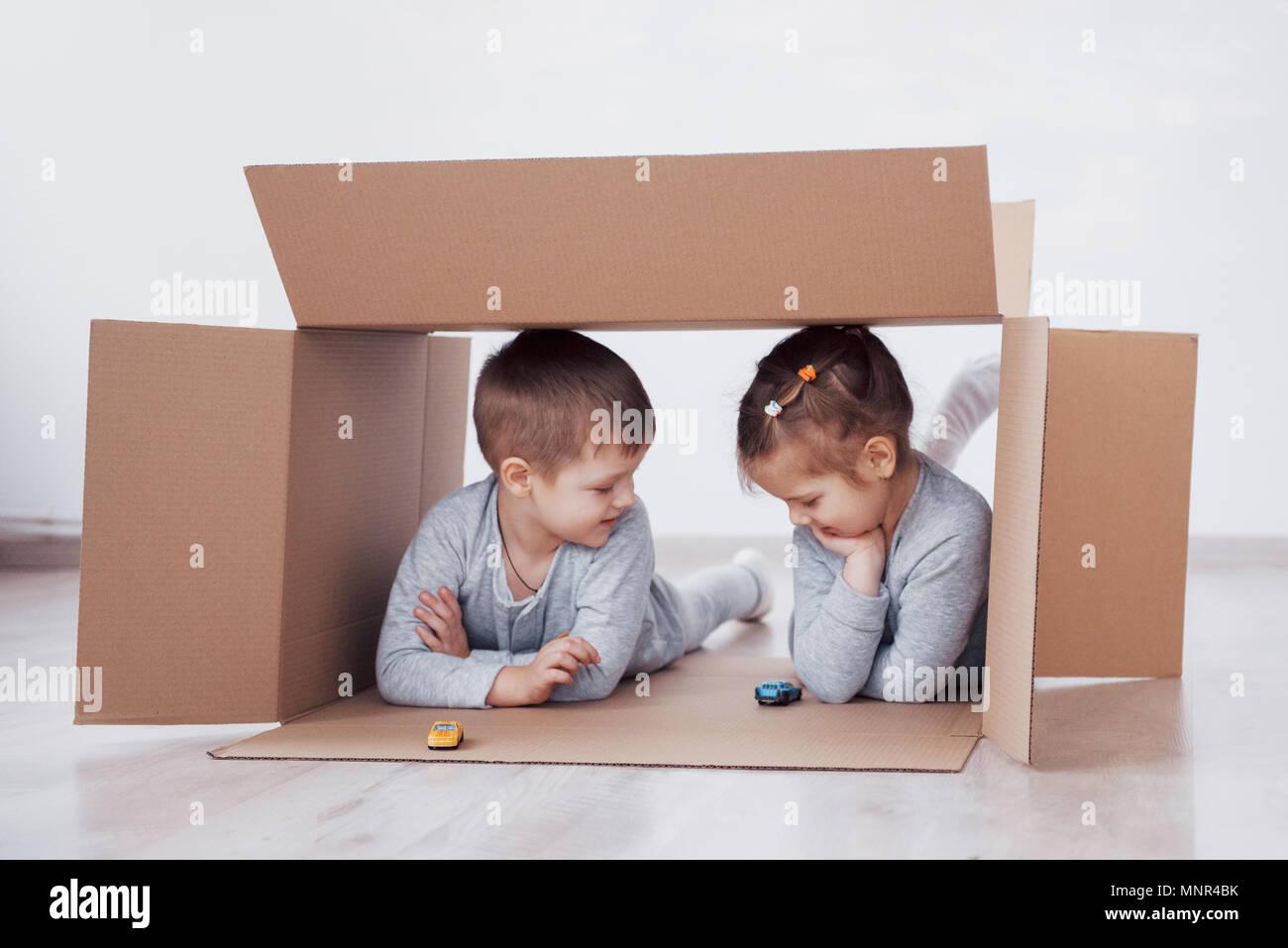 Dos niños pequeños un chico y chica se acaba de mudarse a una nueva casa. Concepto foto .. Los niños se divierten. Foto de stock