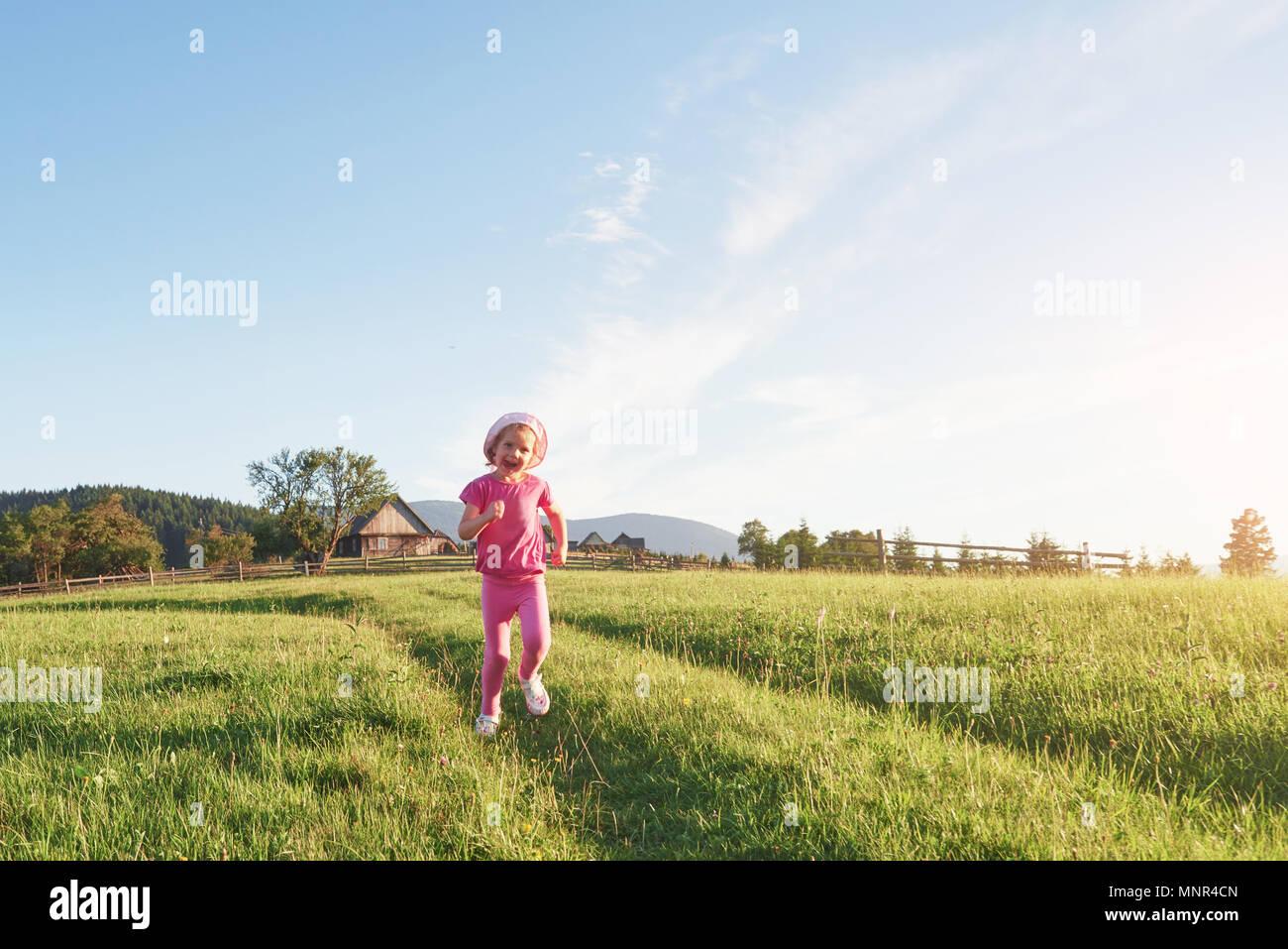 Cute poco feliz niña juegan al aire libre temprano en la mañana en el césped y admirar la vista de las montañas. Espacio para el texto copia Imagen De Stock
