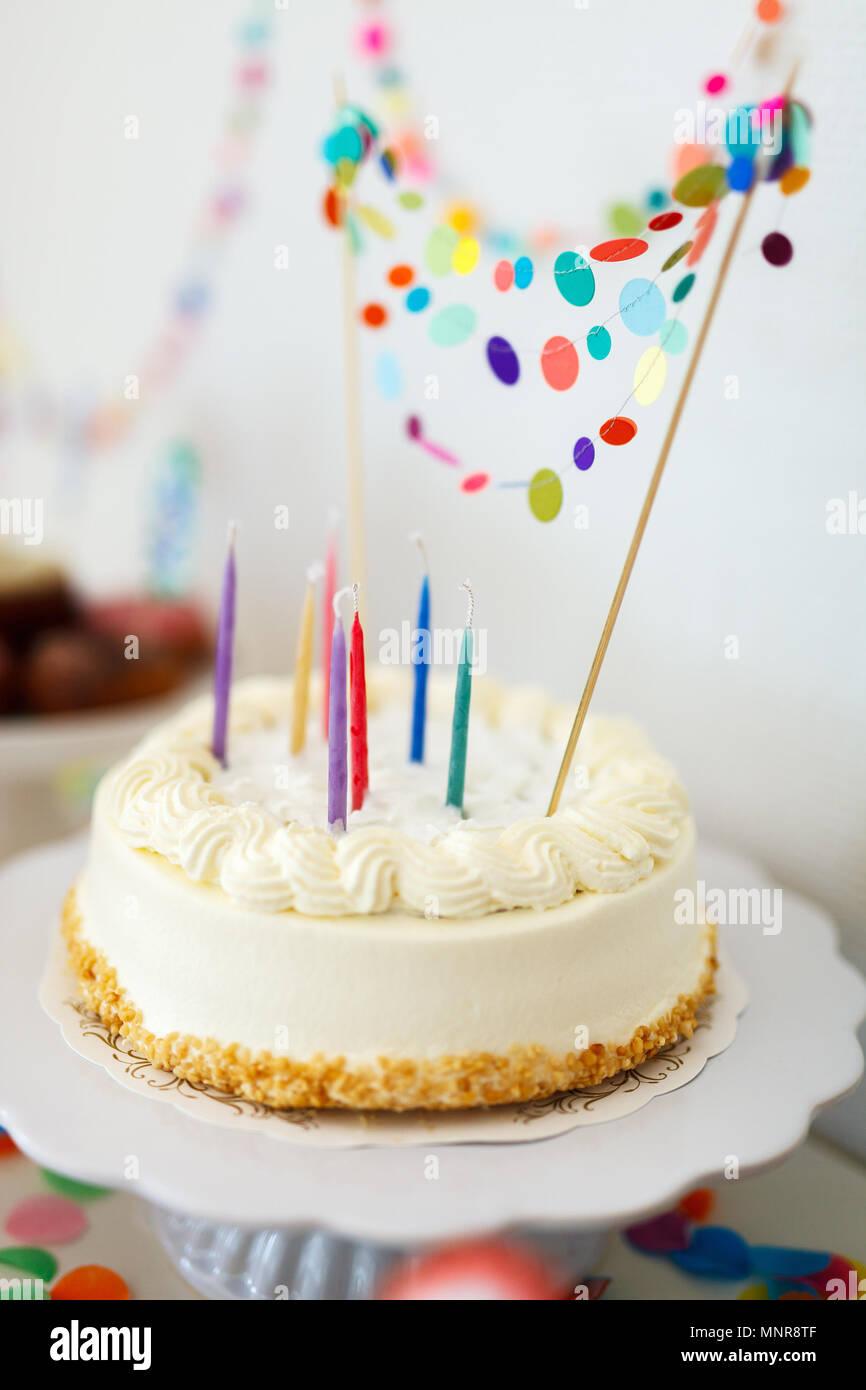 Cerca de un delicioso pastel de cumpleaños decorado con coloridos confeti Imagen De Stock