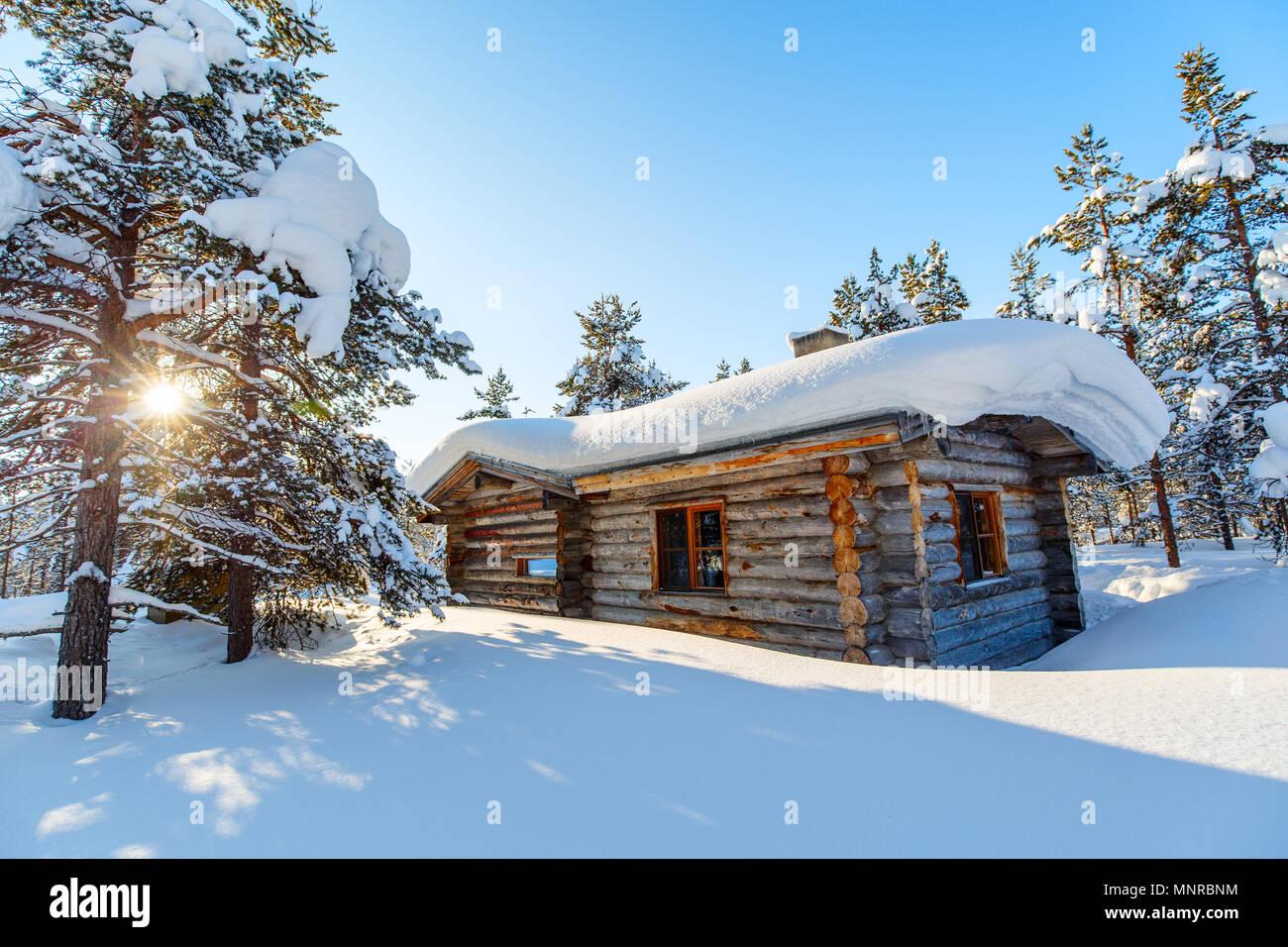 Paisaje invernal con cabaña de madera y árboles cubiertos de nieve Foto de stock