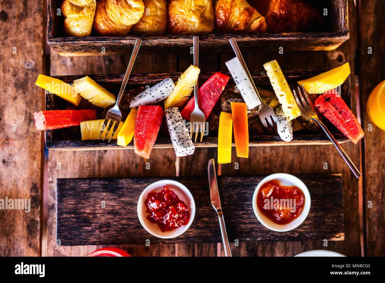 Vista superior de deliciosos alimentos orgánicos para el desayuno servido en la mesa de madera rústica. Frutas, zumos, cruasanes, mermelada y laicos plana. Imagen De Stock