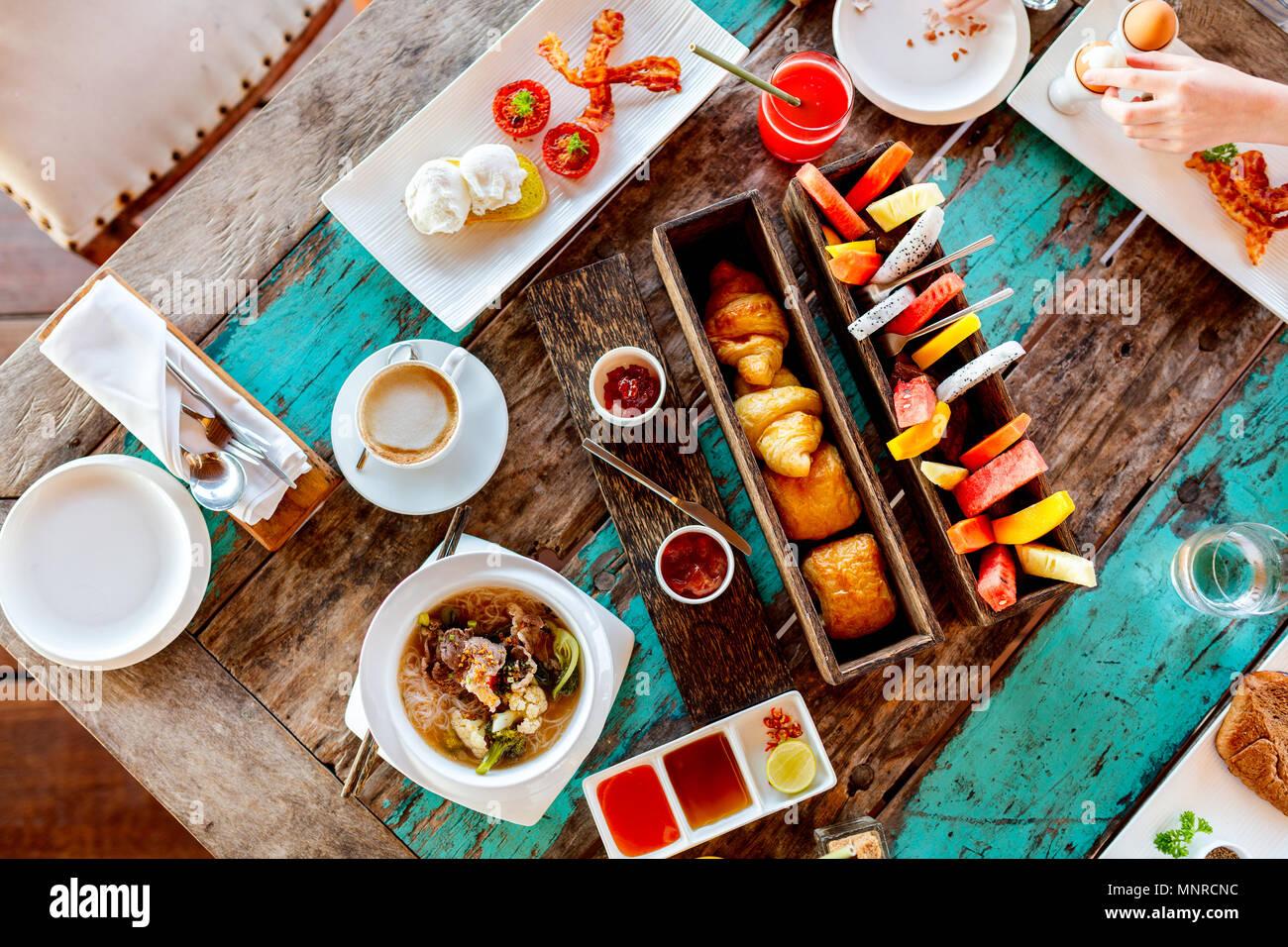 Vista superior de deliciosos alimentos orgánicos para el desayuno servido en la mesa de madera rústica. Café, huevos, frutas, zumos, cruasanes y mermeladas. Imagen De Stock