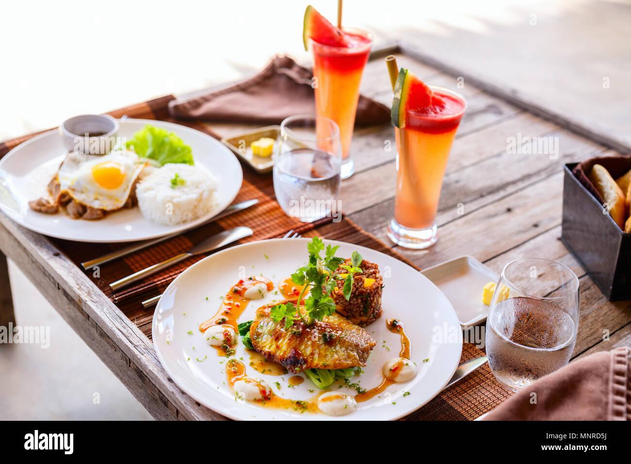 Deliciosa comida para dos en el restaurante de pescado, arroz, huevo frito y verduras verdes Imagen De Stock