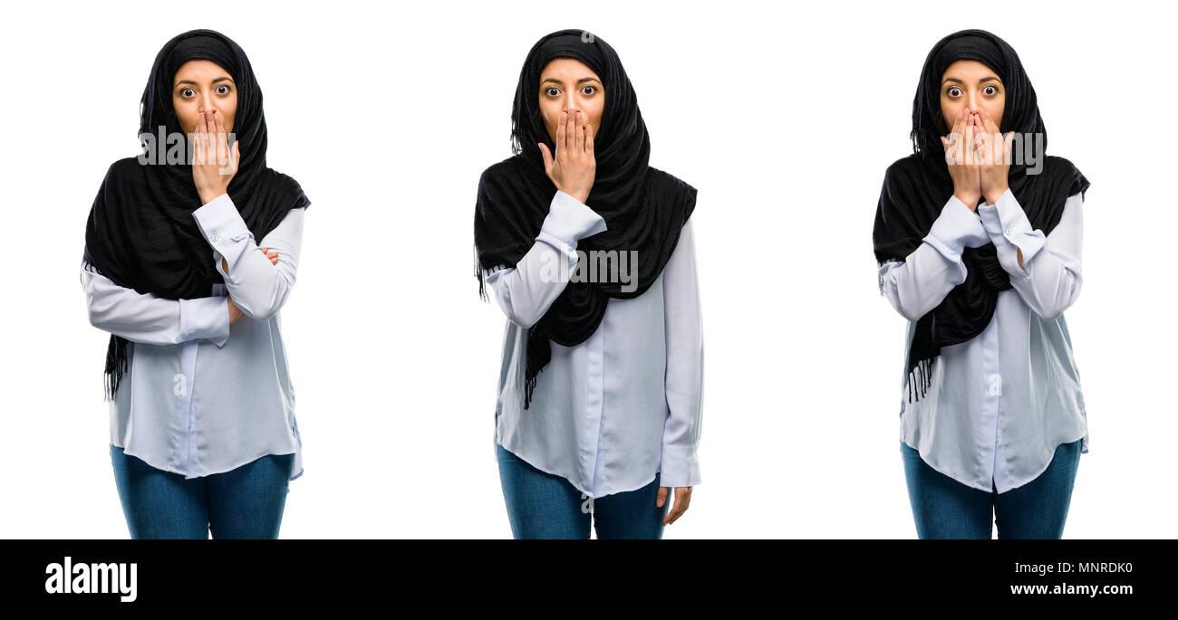 Mujer Árabe llevar hijab cubre boca en estado de shock, parece tímido, expresando el silencio y confundir los conceptos, asustada aislado sobre fondo blanco. Foto de stock
