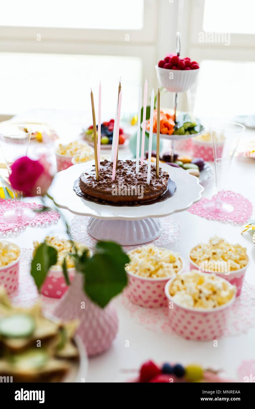 Torta, caramelos, malvaviscos, palomitas de maíz, frutas y otros dulces de postre mesa en la fiesta de cumpleaños para niños Foto de stock