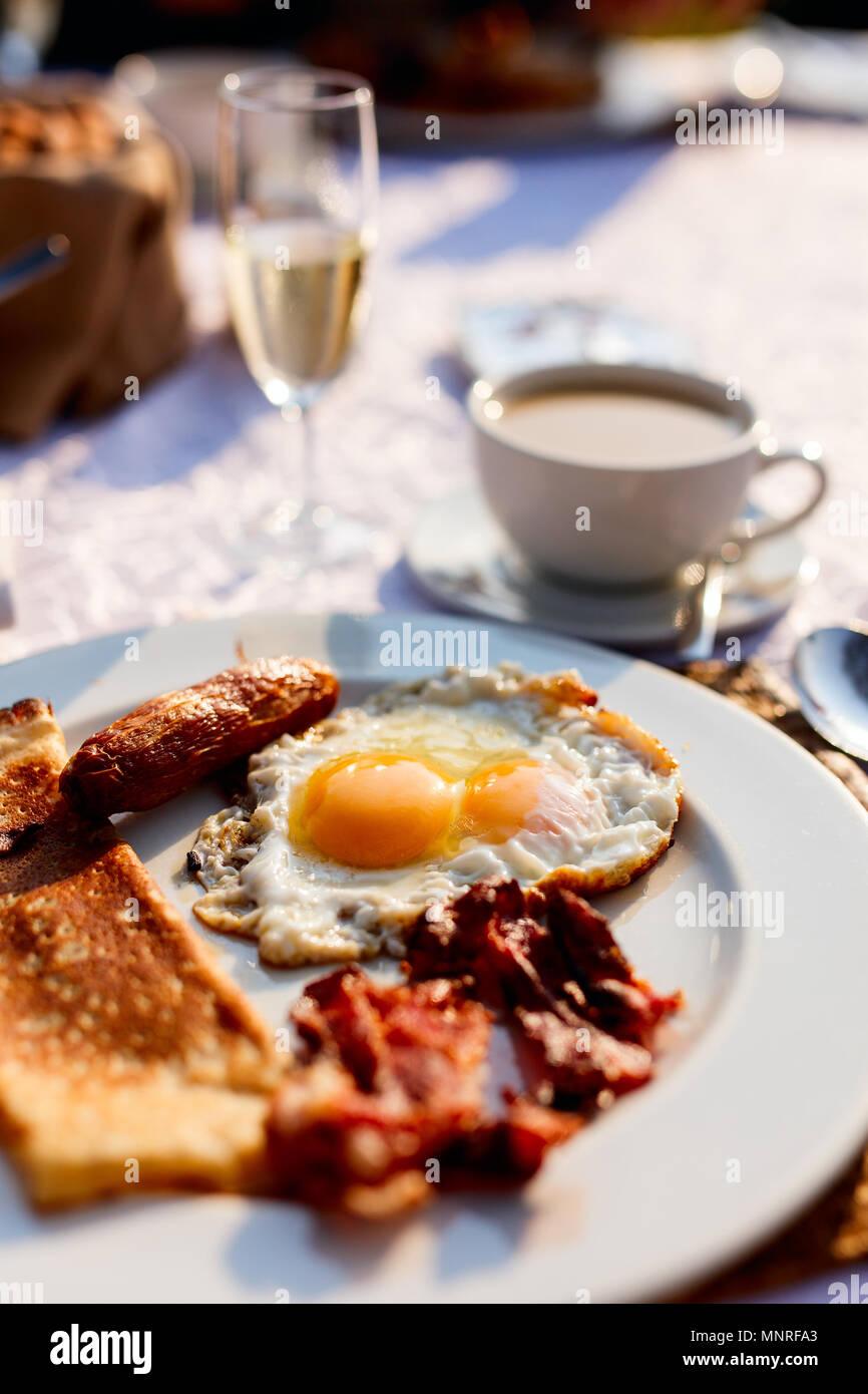 Delicioso desayuno con huevos fritos, tocino y verduras Imagen De Stock
