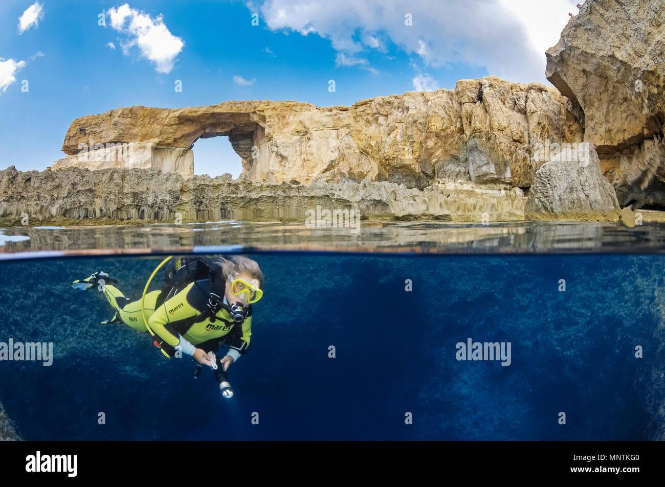 Ventana azul, o ventana de Dwejra, y mujer Scuba Diver en Blue Hole, Gozo, Malta, el Mar Mediterráneo, el Océano Atlántico, el Sr. Imagen De Stock