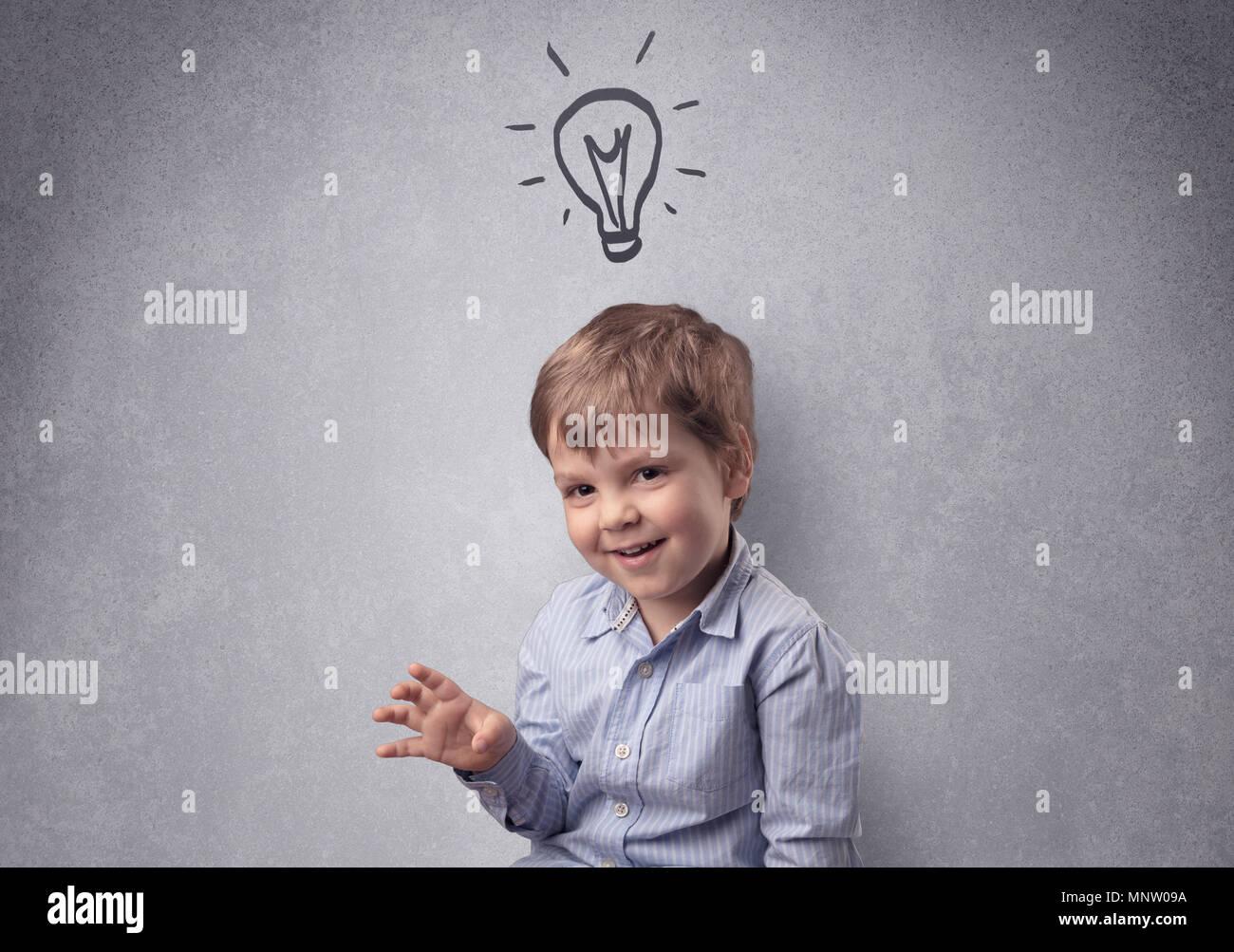 Poco inteligente junior en frente de una pared gris elaborado con concepto infantiles Imagen De Stock
