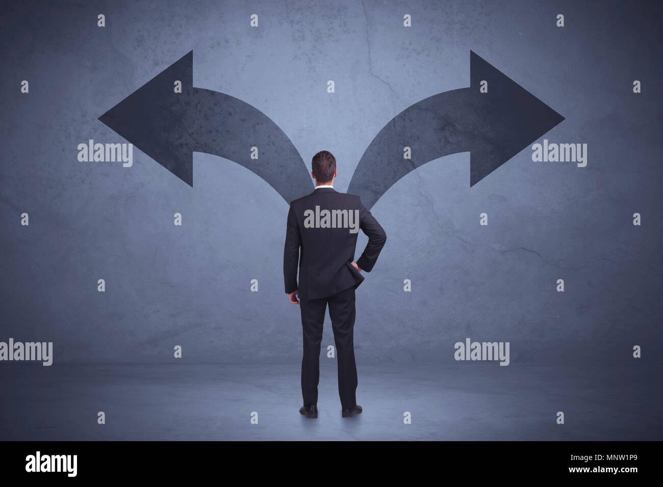 El empresario tomar una decisión mientras mira las flechas en la pared de fondo concepto Foto de stock