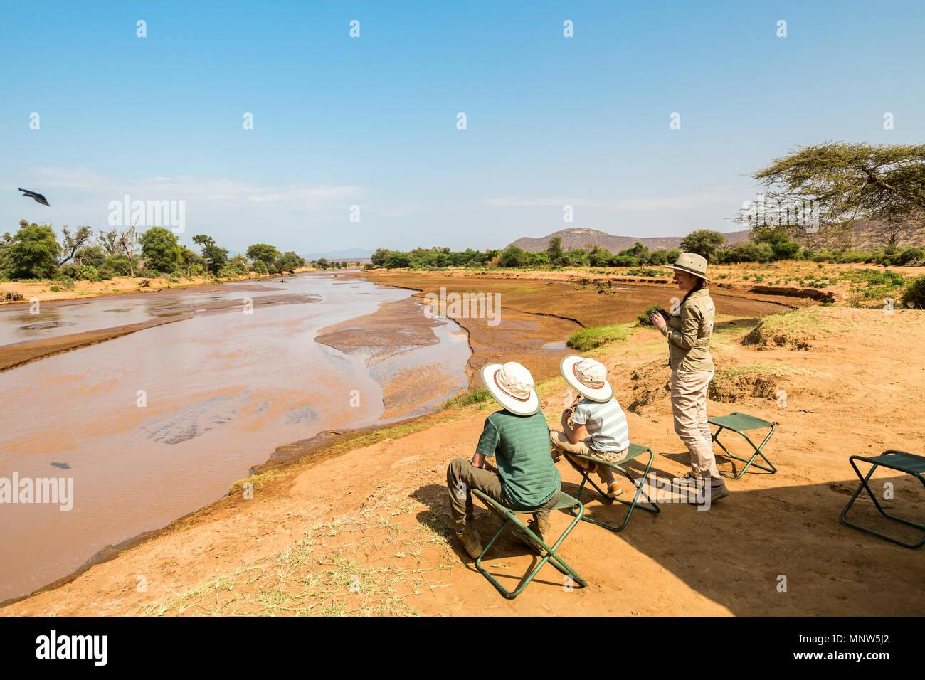 Familia de la madre y los niños en safari africano vacaciones disfrutando de las vistas del río Ewaso Nyiro en Samburu Kenia Imagen De Stock