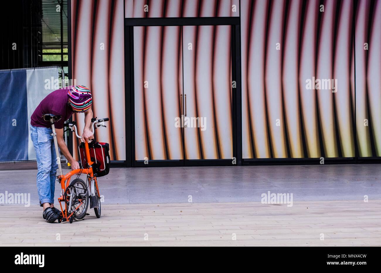 Hombre que llevaba un colorido unforlding stripey casco de bicicleta bicicleta plegable contra un fondo stripey en Kings Cross, Londres, Inglaterra, Reino Unido. Imagen De Stock