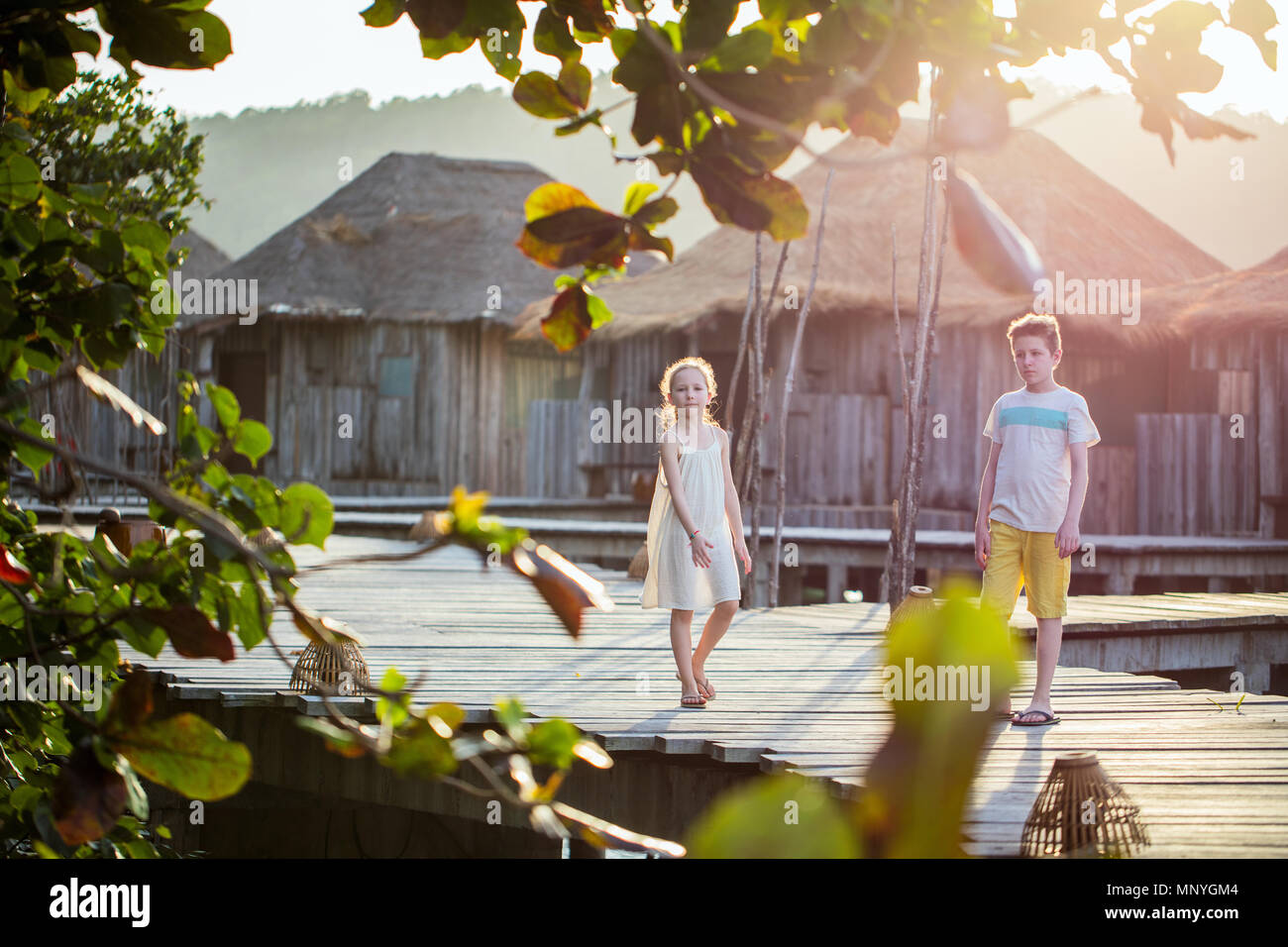 Los niños hermano y hermana caminar sobre la pasarela de madera durante las vacaciones de verano en el resort de lujo Imagen De Stock