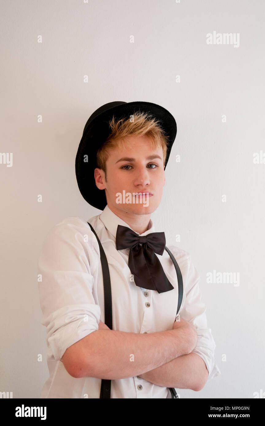 Joven llevar sombrero, tirantes y pajarita. Foto de stock