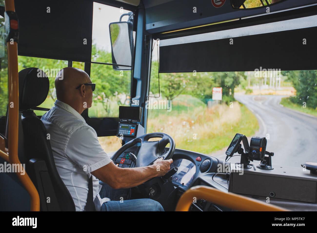 El tema es la profesión de conductor y transporte de pasajeros. Un hombre en gafas de sol un conductor acciona un autobús regional turística en la región de Francia Imagen De Stock