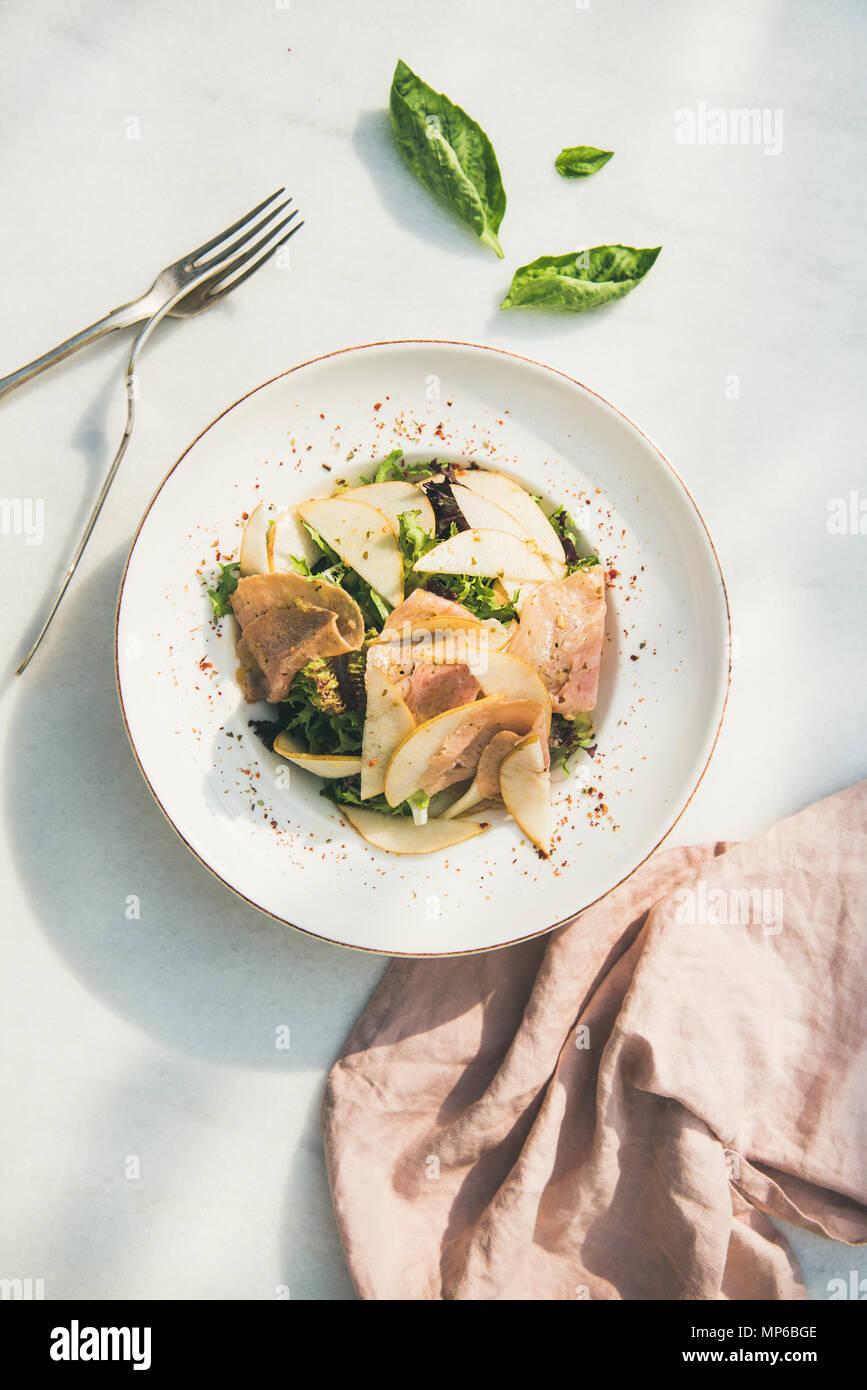 Ensalada de verano con jamón de pavo ahumado y pera, fondo blanco. Imagen De Stock