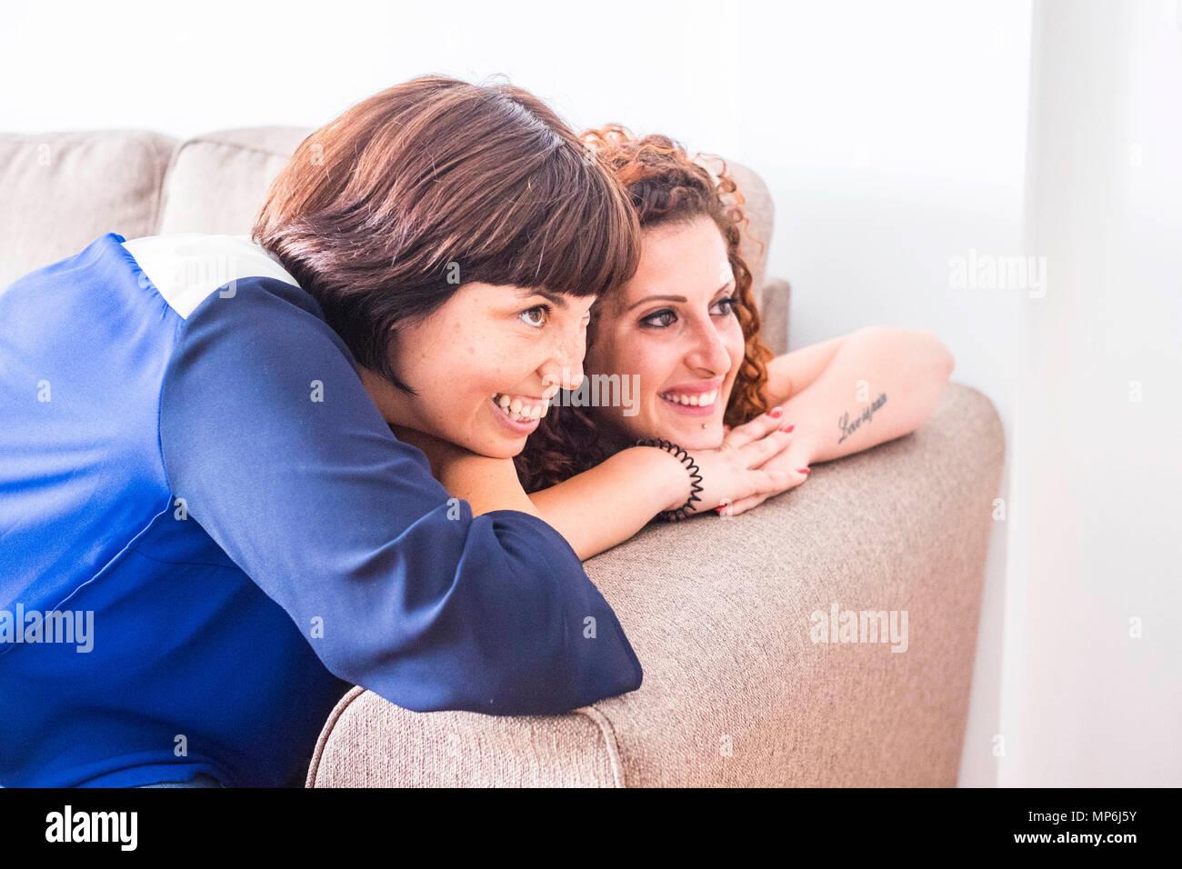 Par od dos amigas permanezcan juntos en el sofá sonriendo y divertirse. La amistad o la relación en casa con interiores de estilo de vida agradable manera Foto de stock