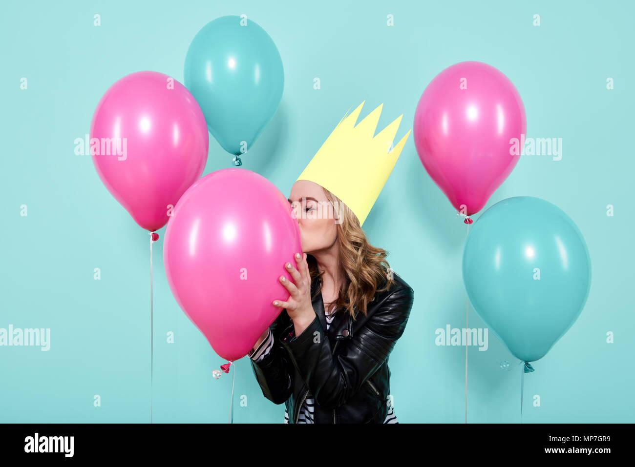 Hermosa joven con chaqueta de cuero y gorro de fiesta kissing balloon colorida, aislado sobre fondo de color azul pastel. Concepto de fiesta de cumpleaños. Imagen De Stock