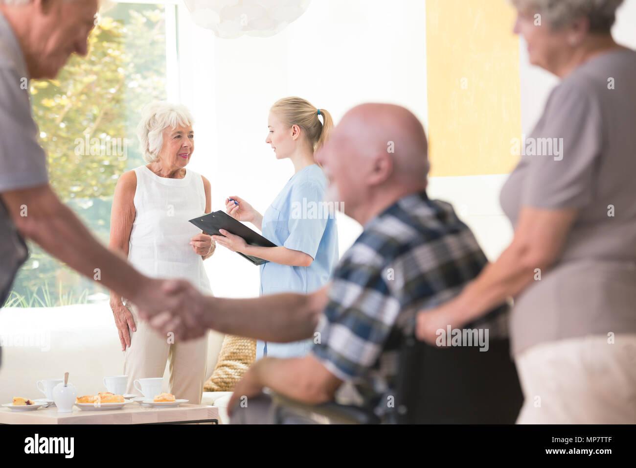 Senior mujer hablando con una enfermera durante una reunión en el salón de casa de descanso Foto de stock