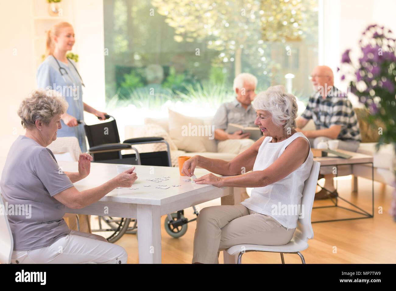 Las mujeres mayores disfrutando de su tiempo juntos mientras está sentado en una mesa y haciendo un puzzle en casa de enfermería Foto de stock