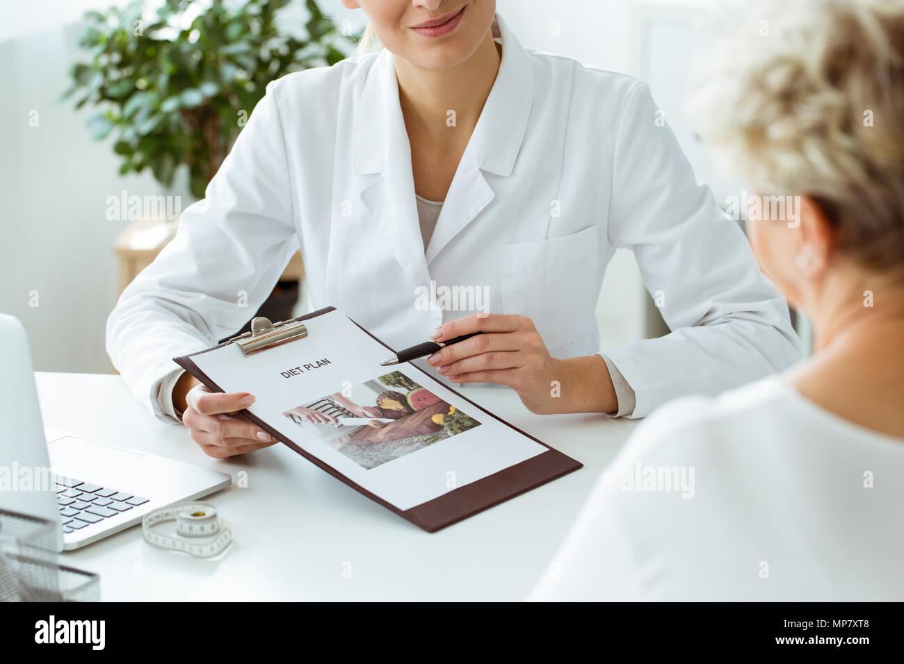 Close-up de la nutricionista mantiene un plan de dieta personalizada para un paciente durante la cita en la clínica Imagen De Stock
