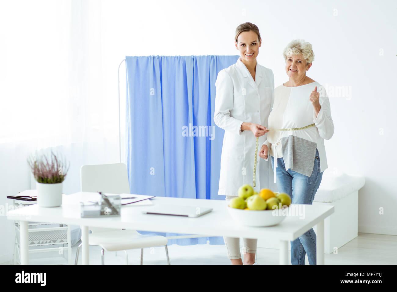 Paciente feliz y sonriente dietista satisfecho con los resultados de la dieta personalizada Imagen De Stock