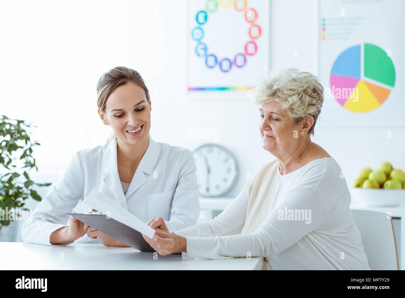 Nutricionista sonriente mostrando personalizado plan de dieta de pérdida de peso a su paciente senior Imagen De Stock