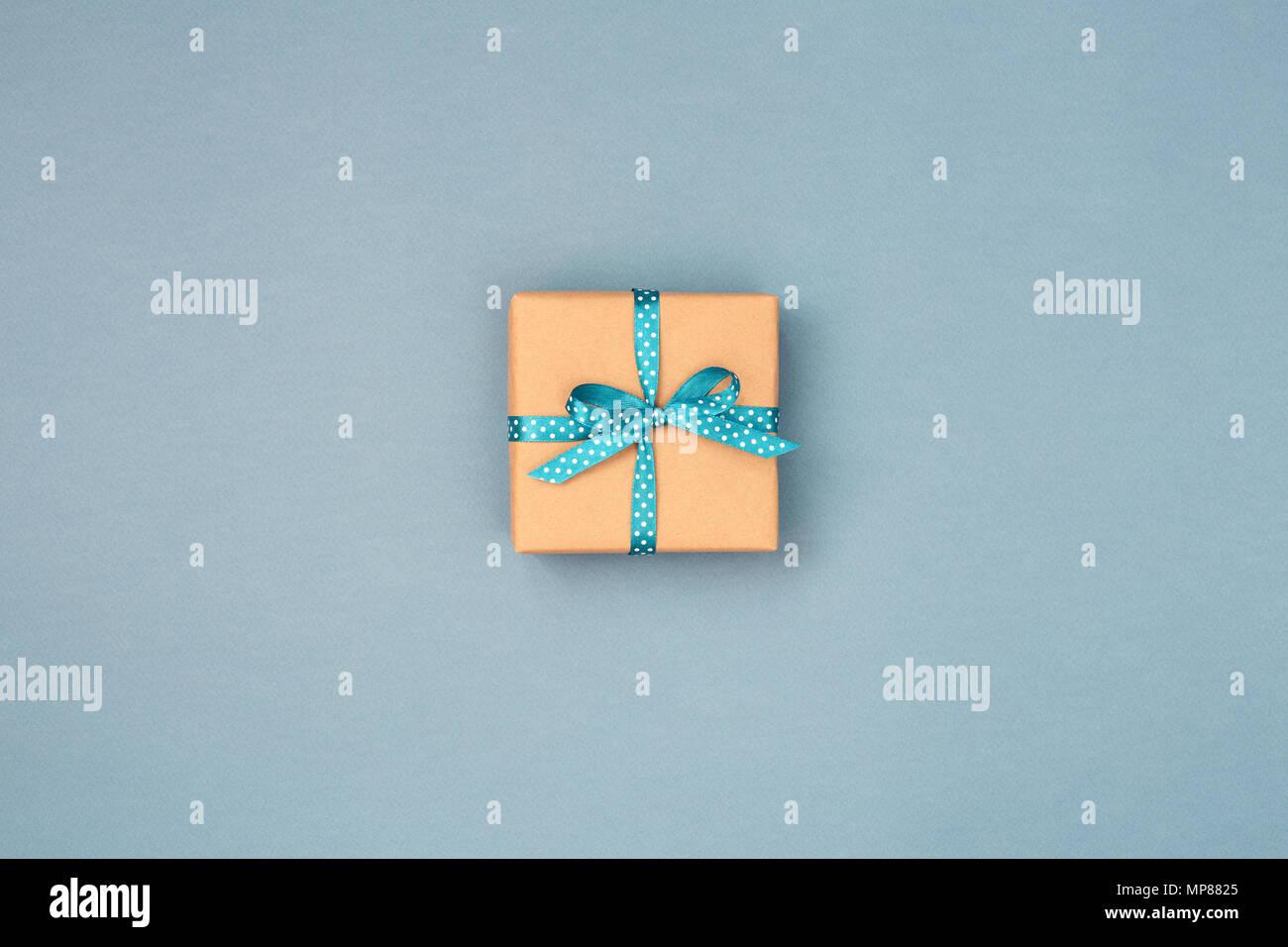 451f3620a Una caja de regalo envueltos en papel kraft atados con blue ribbon en  lunares azules sobre