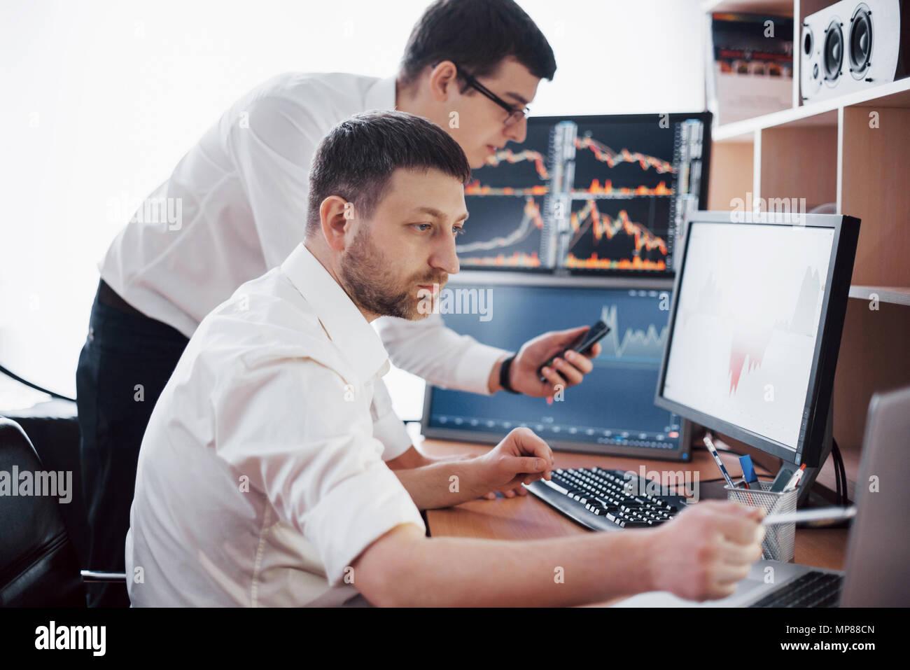 Las existencias comerciales de empresarios en línea. Corredores de Bolsa mirando gráficos, índices y números en varias pantallas de ordenador. Colegas de la discusión en los comerciantes office. Concepto de éxito empresarial Imagen De Stock