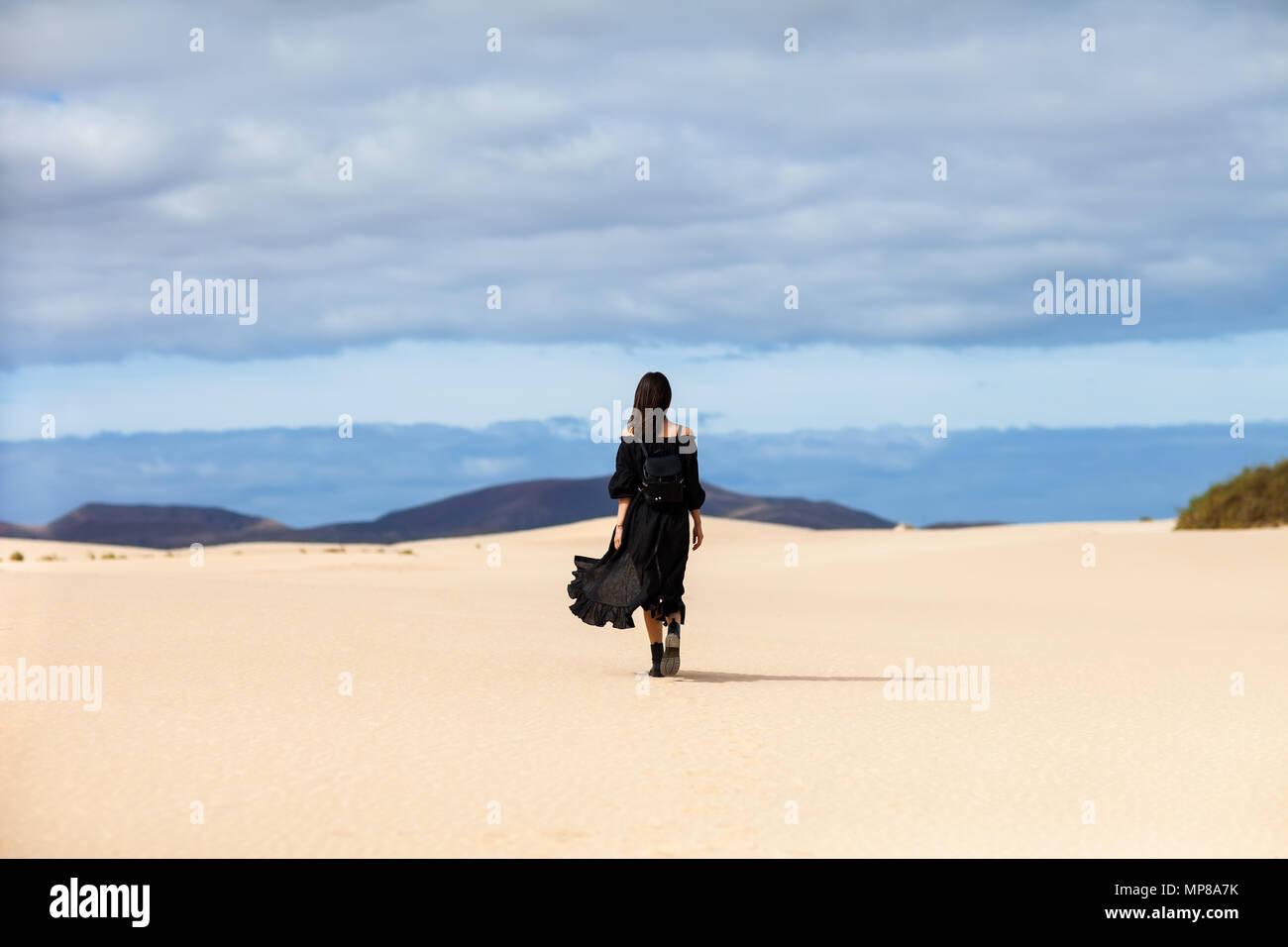 Longitud total retrato de mujer solitaria camina lejos en el desierto, en las Islas Canarias. Concepto de viaje Imagen De Stock