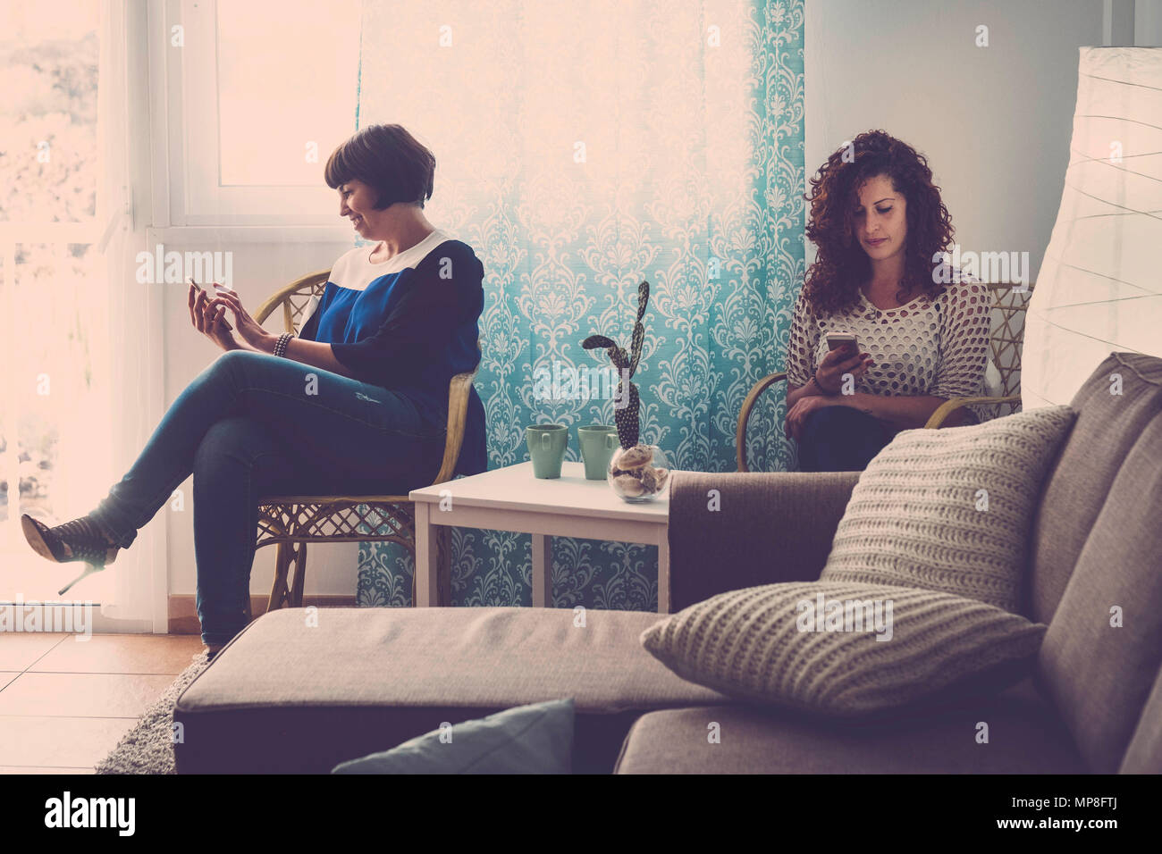 Dos mujeres amigos en casa, todos con un teléfono móvil y chat buscar o revisar el correo electrónico. No hablan entre sí en una moderna tecnología destruir amigo. Imagen De Stock
