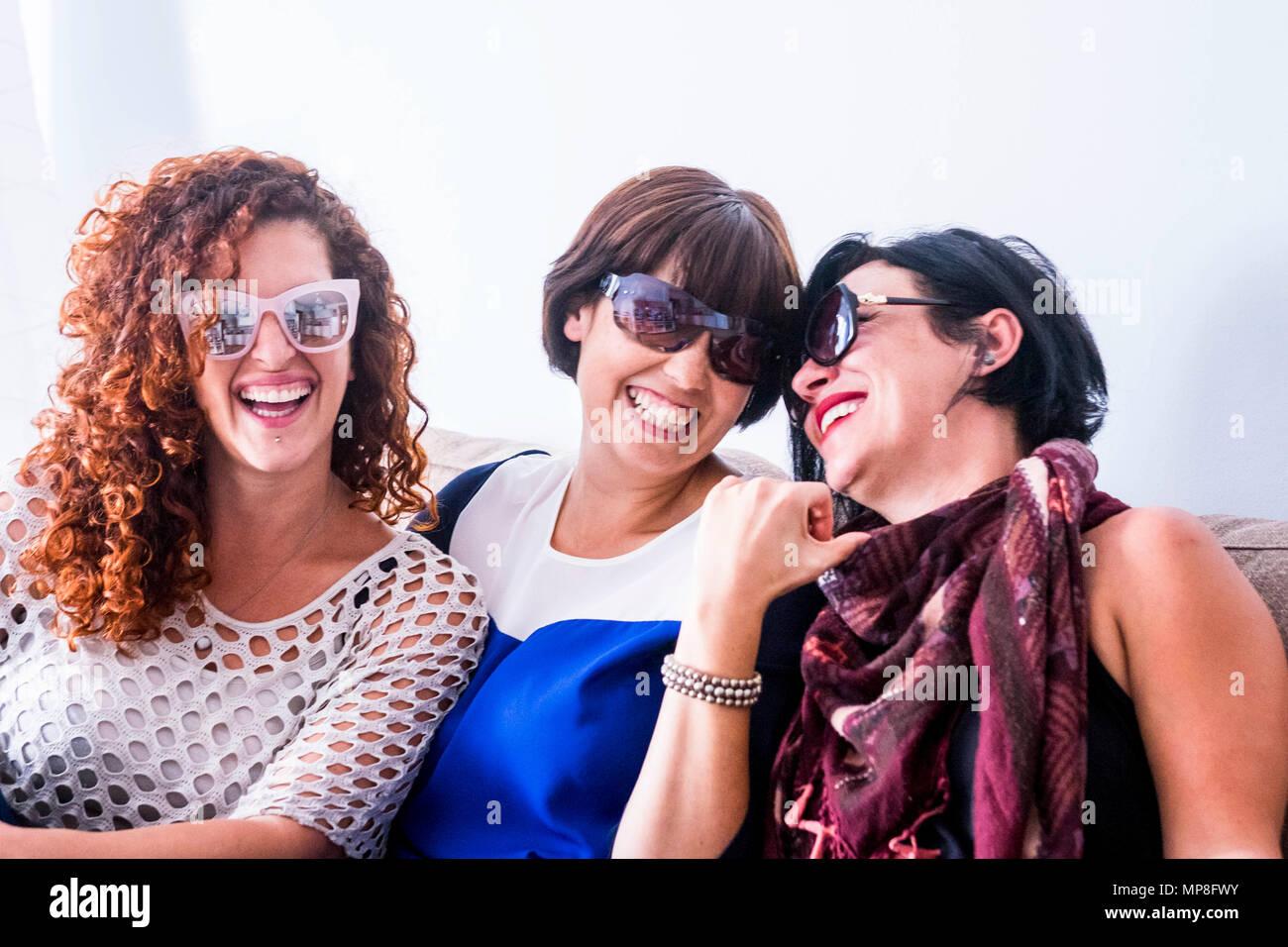 Tres jóvenes mujeres loco amigos tener un montón de diversión en casa en el sofá. Todos ellos con gafas de sol y laughi y sonrisas. cerrar contacto para mejor f Imagen De Stock