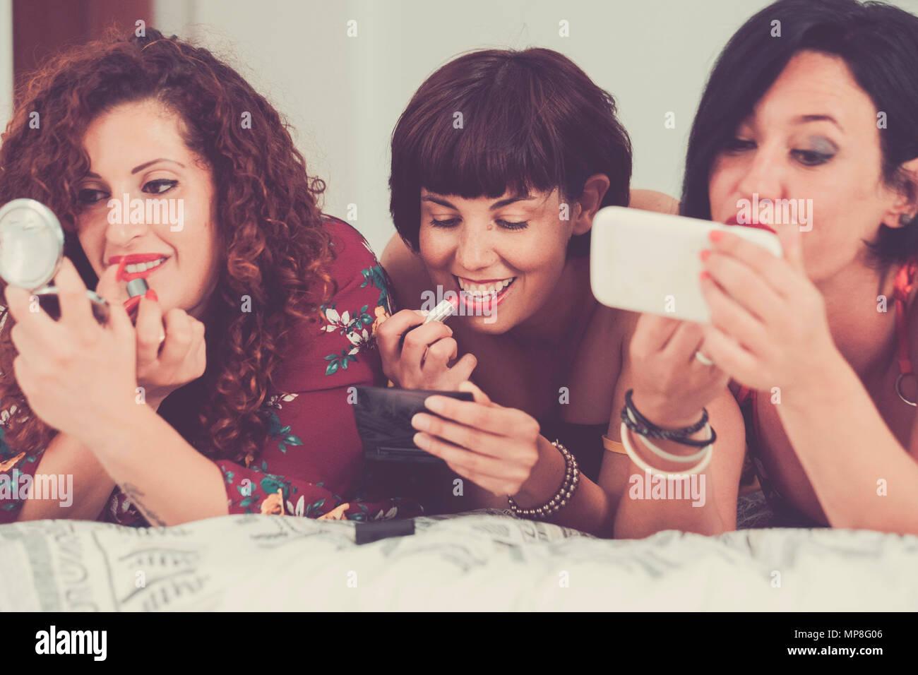 Tres mujeres amigos permanecen junto a echarse sobre la cama haciendo maquillaje antes de ir a las fiestas de noche. amistad concepto uno de ellos usan un móvil p Imagen De Stock