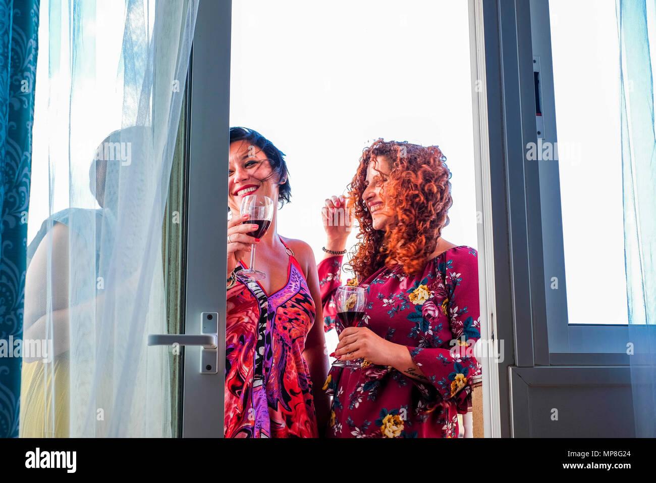 Tres jóvenes mujeres caucásicas en casa en la terraza al aire libre haciendo fiesta y fiesta bebiendo una copa de vino. la sonrisa y la felicidad de la amistad Imagen De Stock