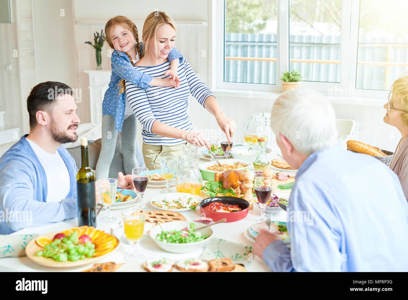 Feliz madre sirviendo comida en la cena familiar. Imagen De Stock