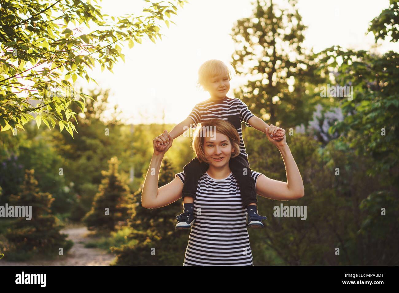 Madre e hijo en rayas T-shirts. Mujer sosteniendo boy en piggieback. La familia juntos. Divertirse Imagen De Stock
