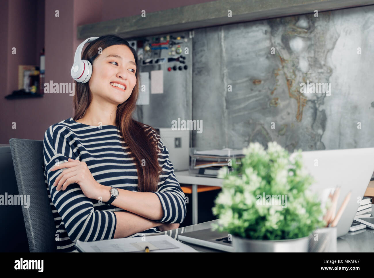 Los jóvenes asiáticos empresaria casual el brazo en posición de descanso de escritorio con ordenador portátil y escuchar música a través de auriculares, y mirando a través de la ventana de la oficina ,trabajo Foto de stock