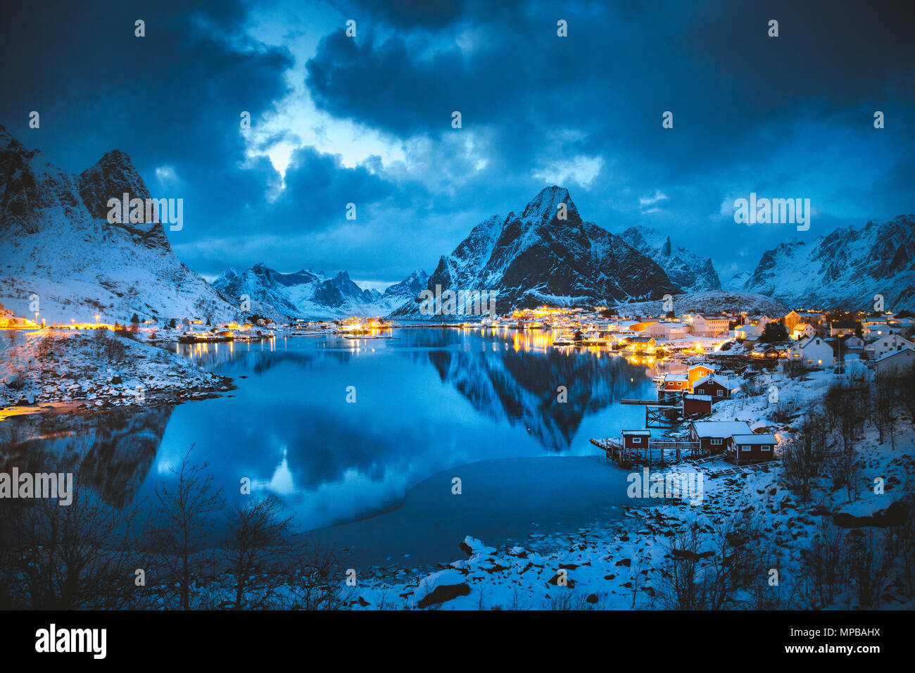 Vista clásica de la famosa aldea de pescadores de Reine con Olstinden pico en el fondo en la mágica noche de invierno crepúsculo, Islas Lofoten, Noruega Foto de stock